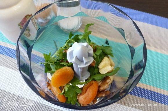 В чашу блендера сложить курагу, чеснок, грецкие орехи, петрушку.