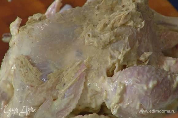 Замаринованного цыпленка выложить на бумажное полотенце и через разрезы пальцами отделить кожу от тушки, так чтобы получились большие карманы, наполнить их пряным маслом, затем сверху смазать цыпленка оставшимся маслом.