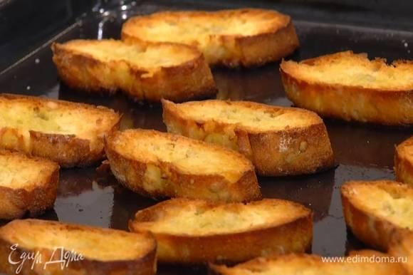 Багет нарезать тонкими ломтиками, выложить на противень, сбрызнуть оставшимся оливковым маслом и подсушивать в разогретой духовке 2–3 минуты.