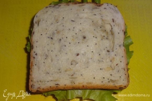 На помидоры положить второй салатный лист, на салат положить намазанный маслом хлеб (маслом вниз).