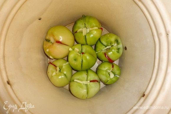 На дно эмалированного ведра или кастрюли уложить слой фаршированных помидоров.