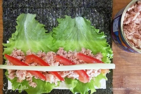 На листья салата в первом случае выкладываем салатный тунец (он более нежный по текстуре и более соленый). На тунец кладем помидор и огурец. Сворачиваем рулетом.