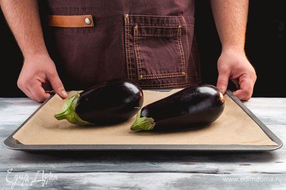 Баклажаны вымыть, выложить на пергамент и запекать без масла в течение 30 минут при температуре 220°C.