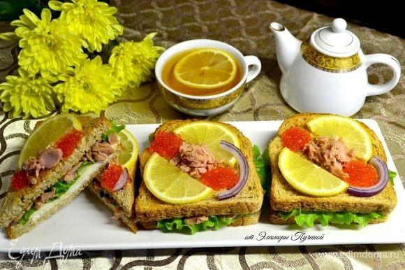 Далее кусок хлеба, обжаренный в тостере до золотистой корочки, и сверху на него красиво разложить дольки лимона и икру, в центр — кусочки тунца. Украсить кольцом красного лука.