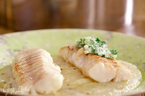 Выложить на тарелку пюре, сверху — треску. Дополнить рыбу ароматным маслом с чесноком и петрушкой.