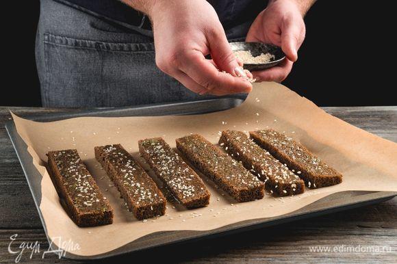 Посыпьте гренки кунжутом и выпекайте при температуре 180°C в течение 10–15 минут.