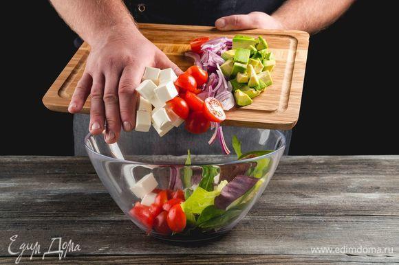 Порвите салатные листья руками и застелите блюдо. Выложите горкой вперемешку авокадо, фету, томаты и красный лук.