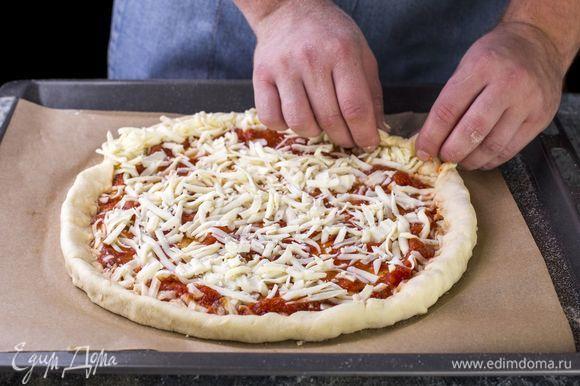 Раскатайте тесто, переложите его на бумагу для выпечки. В центр налейте небольшое количество соуса. Посыпьте тесто сверху тертой моцареллой, распределяя по краям большую ее часть. Защипните края. Сверху выложите начинку.