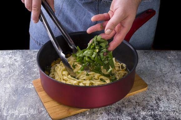 Лапшу и базилик добавьте в сковороду.
