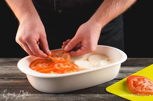 Выложите слой из колец лука и кружков помидора. Посыпьте сыром.