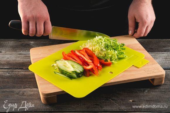 Нарежьте тонкой длинной соломкой огурец, сладкий перец, пекинскую капусту, используя разделочную доску Faberlic by Julia Vysotskaya.