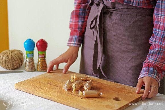 Выложите на середину каждого квадрата 2 ч. л. куриного фарша и заверните пленку трубочкой. Один конец завяжите ниткой, плотно утрамбуйте мясную смесь и завяжите второй конец трубочки.