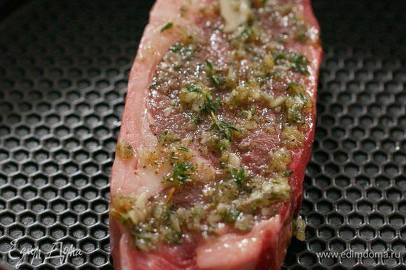 Выложить стейк на горячую сковороду чистой стороной, без специй. Жарить 2–3 минуты.