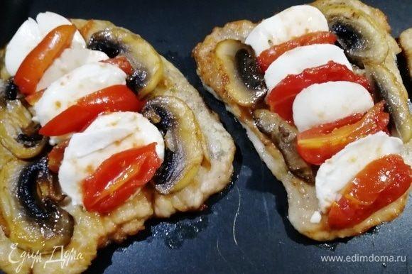 Выкладываем на мясо помидоры, моцареллу и шампиньоны. Ставим противень в духовку, разогретую до 180°С, на 15 минут.