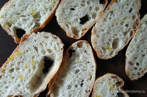 Теперь сами брускетты. Для хрустящей снаружи, но мягкой внутри основы нарезаем чиабатту кусочками толщиной 0,8–1 см, сбрызгиваем слегка оливковым маслом и обжариваем на раскаленном гриле с обеих сторон.