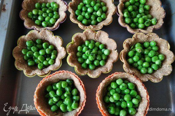Выкладываем на тесто зеленый горошек.