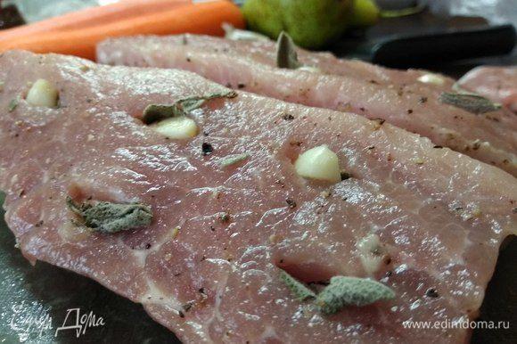 Берем часть свинины, пригодную для запекания. Лучше всего вырезку. Если кусок крупный, то разрезаем его на 2 части. Очищаем от пленок и жира, смазываем оливковым маслом и натираем солью. Делаем ножом надрезы по всей поверхности и кладем в них разрезанные на несколько частей зубчики чеснока и целые листики шалфея.