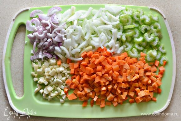 Овощи помыть, очистить. Лук нарезать полукольцами (разрезать еще пополам), морковь — мелкими кубиками, чеснок крупно порубить, сельдерей нарезать полукольцами.