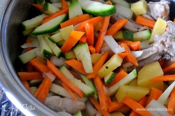 На курицу выкладываем все нарезанные овощи. Заливаем крутым кипятком и варим до готовности картофеля.