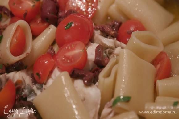 Шумовкой переложить отваренные макароны в сковороду с рыбой, добавить помидоры и оливки и прогревать еще несколько минут, затем посыпать пасту петрушкой с чесноком и миндалем, сбрызнуть оливковым маслом Extra Virgin и выключить огонь.