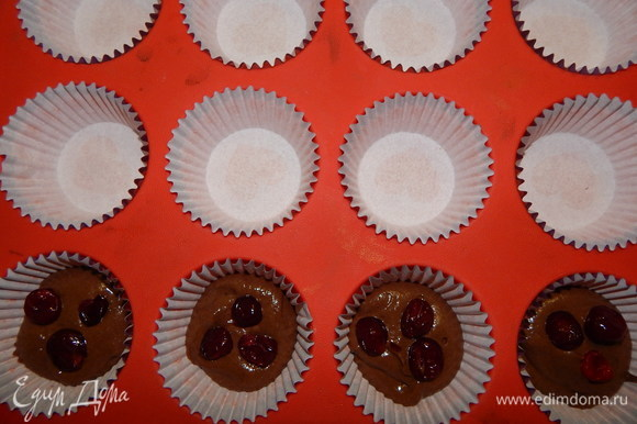 В формы для кексов вложить бумажные капсулы, выложить по 1 ст. л. теста, положить по 3 ягодки и доложить тесто, заполнив форму на 3/4. Выпекать кексы в разогретой до 180°C духовке 20–25 минут.