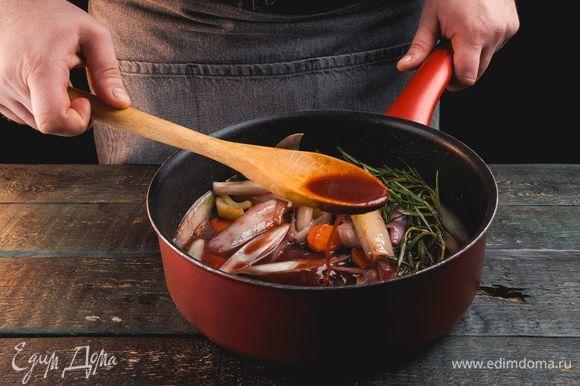 Добавьте к овощам томатную пасту и розмарин, влейте вино в сковородку, продолжайте жарить.
