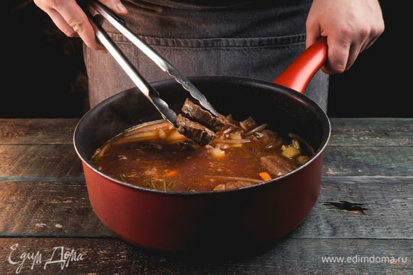 Тушите, пока жидкость не уменьшится вдвое. Затем влейте бульон, доведите до кипения и добавьте мясо. Варите 2–2,5 часа.