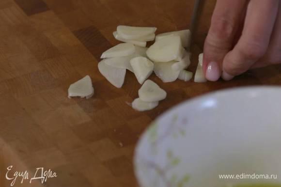 Чеснок почистить и нарезать тонкими пластинками.