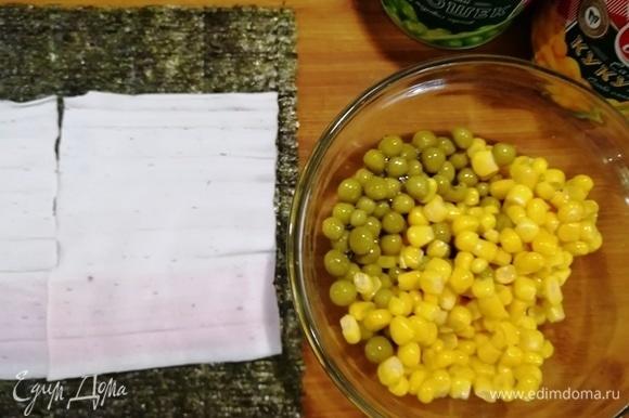 Подготовим кукурузу и зеленый горошек. На лист нори уложим развернутые крабовые палочки.