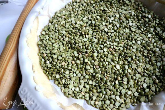Положить на тесто в форме лист пергамента, горох или другой натуральный или искусственный наполнитель. Отправить в предварительно разогретую духовку на 15 минут.