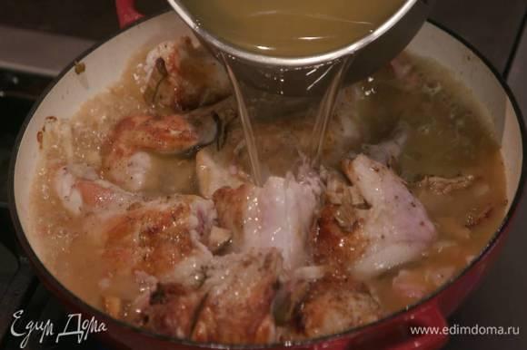 Влить в сковороду белое вино, воду, в которой замачивались грибы, и куриный бульон, так чтобы мясо было почти покрыто жидкостью.