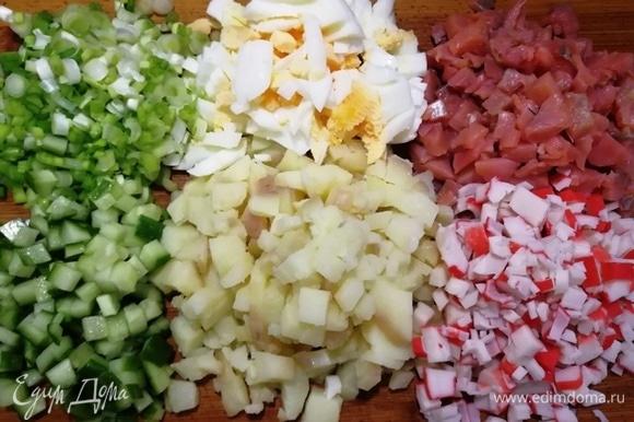 Для салата возьмем отварной картофель среднего размера, яйца некрупные (С1), крабовые палочки, огурчик средний (без сердцевины), белую часть зеленого лука, слабосоленый лосось. Все ингредиенты нарежем одинаковым кубиком.