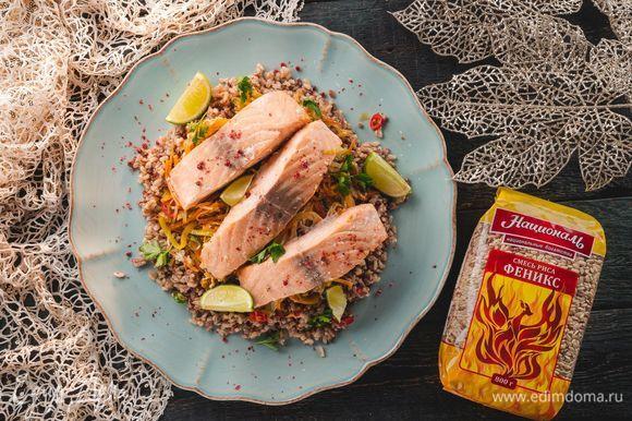 Достаньте противень из духовки и оставьте на 5 минут. Выложите рис на блюдо. Сверху — рыбу и овощную смесь. Ароматное праздничное блюдо готово!