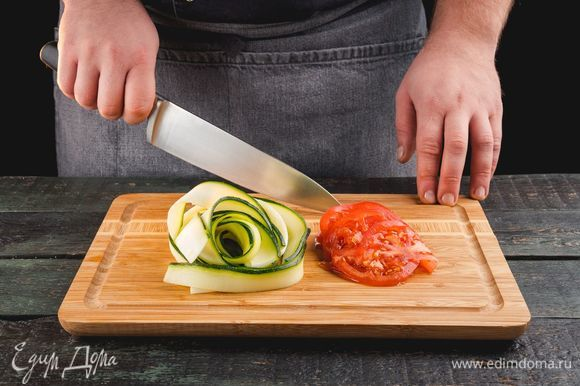 Нарежьте цукини и помидоры.