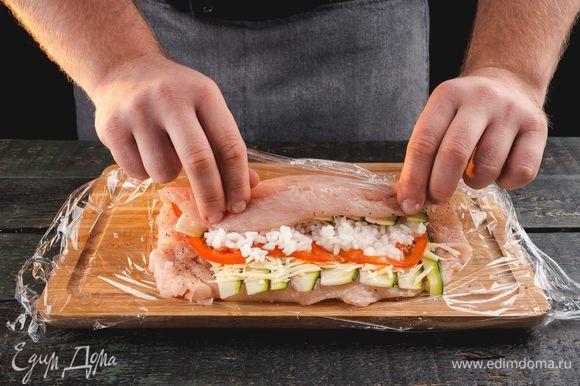 Выложите сверху рис тонким слоем. Аккуратно сверните курицу в рулет и скрепите зубочистками.