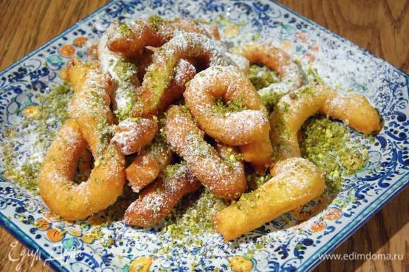 Готовые горячие пончики посыпать измельченными фисташками и сахарной пудрой.
