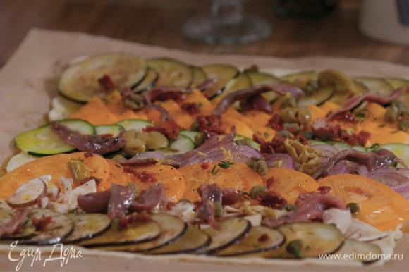 Сверху — немного тимьяна, каперсов, нарезанных оливок, вяленых томатов и анчоусов. Посыпать лимонной цедрой. Выпекать в духовке 15–20 минут.