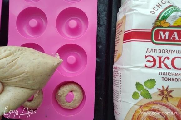 Приготовить формочки для пончиков. Если у вас, как у меня, силиконовые — смазывать не нужно, если тефлон — смазать сливочным маслом. Распределить тесто с помощью кондитерского шприца или пакета с обрезанным краем. Так получаются ровненькие экземпляры.
