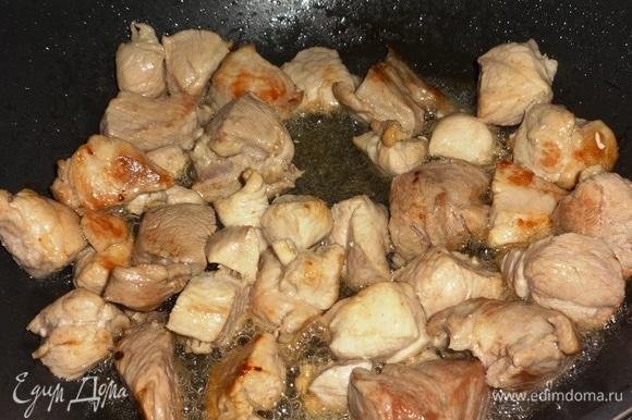 В сковороде разогреть растительное масло и обжарить на нем свинину до румяной корочки, помешивая.