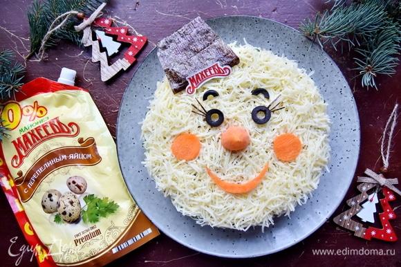 Завершающий слой — натертый на мелкой терке сыр. Салат накрыть пленкой и оставить на некоторое время пропитаться. Перед подачей осталось украсить салат в виде снеговичка или любого другого новогоднего персонажа.