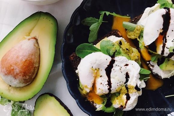 Нарезать тонкими полосками спелое авокадо и выложить на тосты. Поверх авокадо выложить немного руколы.