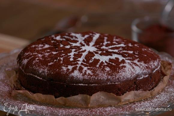 Пока торт горячий, посыпать его сахарной пудрой, затем сверху положить трафарет-снежинку и засыпать ее какао через сито. Снежинку снять, чтобы остался только белый след.