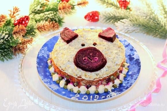 Седьмой слой — яичный желток. Украшаем салат сверху «пятачком», «ушками» из свеклы и «глазками», вырезанными из маслин. Новогодний салат готов!