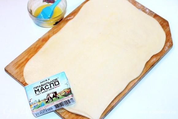 Из этого количества теста выходит 2 больших пирога. Формочки для пирогов диаметром 26 см. Делим тесто на 2 части. С одной частью работаем, другую держим в пакете в холодильнике. Раскатываем тесто в пласт размером 36х27 см без напыления мукой. Смазываем 1/2 часть пласта растопленным сливочным маслом (50 г).