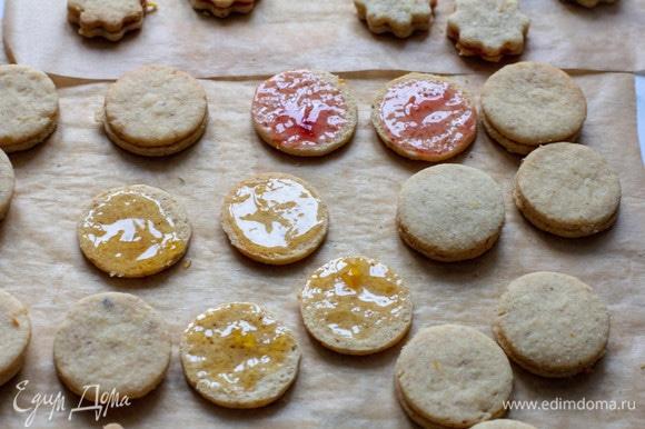 Остывшее печенье попарно склеить с помощью джема (желательно джем перед этим прокипятить в течение пары минут, затем остудить).