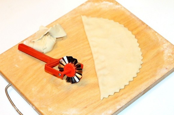 Аккуратно обрежьте специальным колесиком край круга. Остатки теста положите в чашу под полотенце.