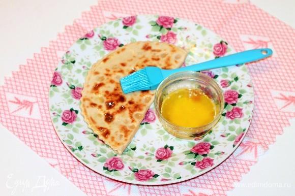 Складывая лепешки стопкой, обильно смажьте их растопленным сливочным маслом.