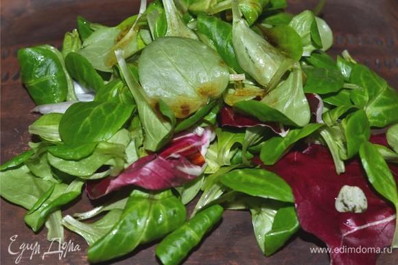 Начинаем собирать наш салат. Выкладываем на блюдо нашу смесь из салатов. Добавляем немного заправки и аккуратно смешиваем листья.