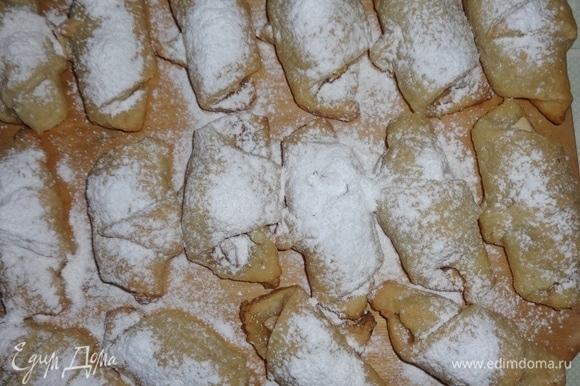Снять рогалики с противня, выложить на доску и посыпать сахарной пудрой.