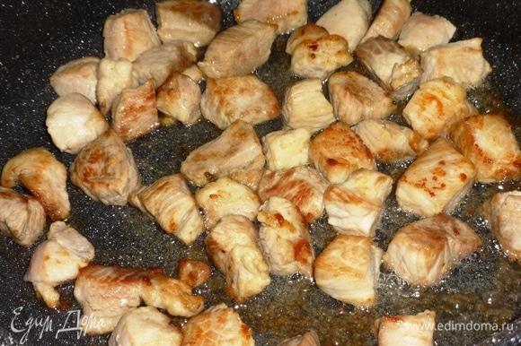 В сковороду налить половину масла и разогреть его. Выложить кусочки свинины и обжарить их на сильном огне до румяной корочки. Выложить мясо в кастрюлю, оставив масло в сковороде.